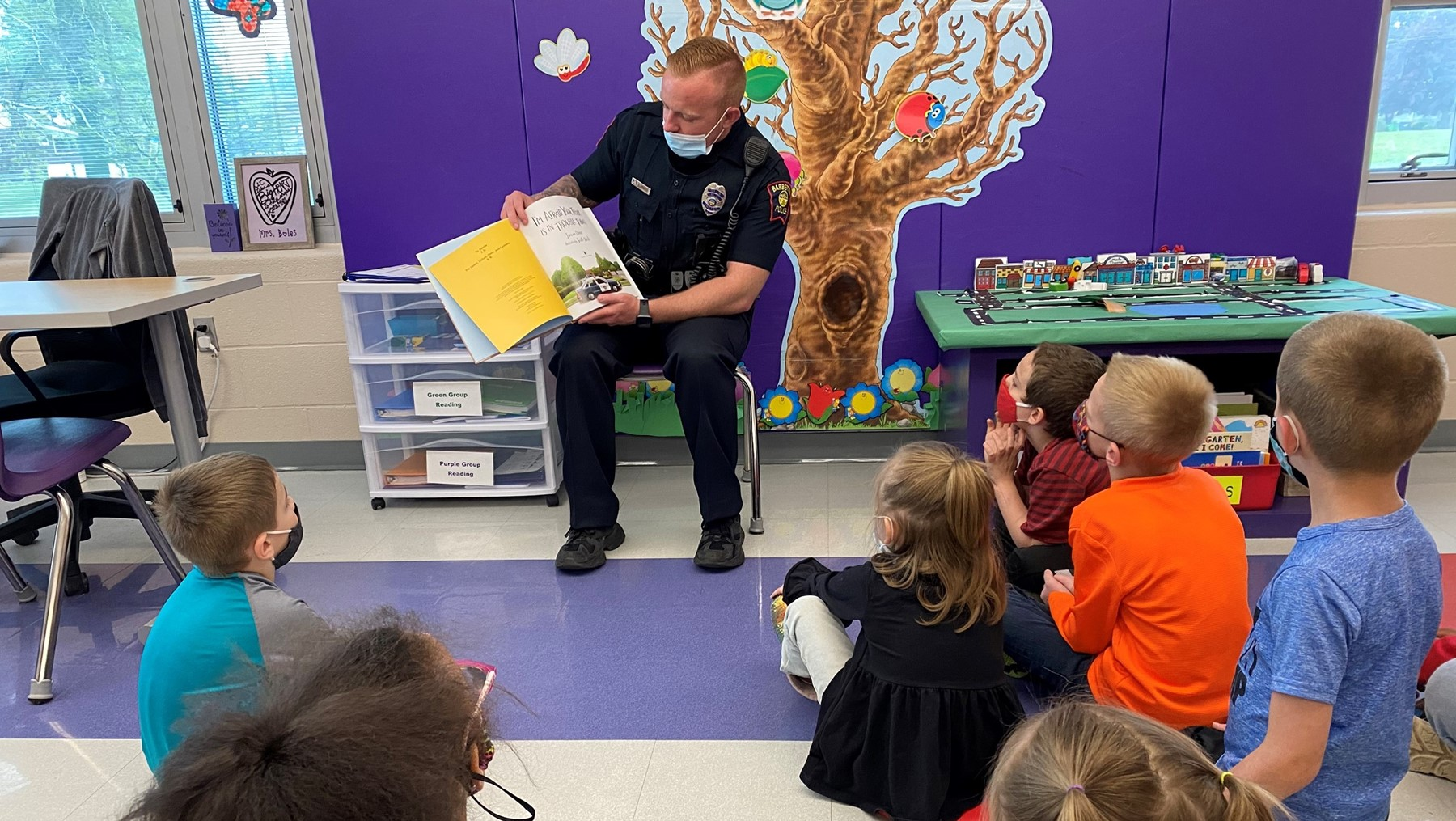 SRO Stalder reads a story to Mrs. Monroe's class @BEW during a lesson on community helpers.